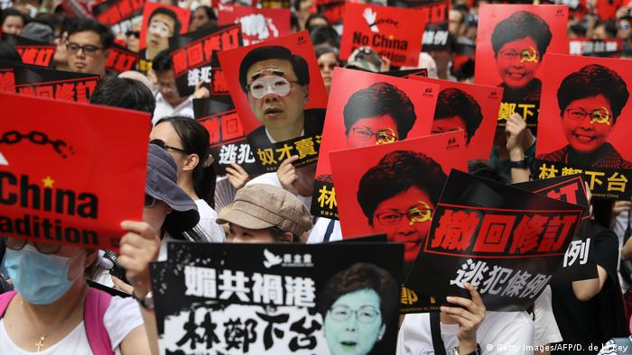 Protesters hold placards bearing images of Hong Kong Chief Executive Carrie Lam and Secretary for Secretary for Security John Lee (top C) during a rally against a controversial extradition law proposal in Hong Kong on June 9, 2019.