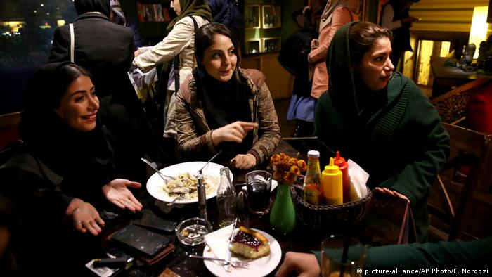 Women sit around a table in a cafe in Tehran