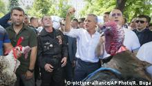 Vladimir Plahotniuc, the leader of the Moldova's Democratic party, and the country's de facto leader, clenches his fist gesturing next to interim president Pavel Filip, right, as people hold turkeys before throwing them over the fence of the Modovan presidency building in Chisinau, Moldova, Sunday, June 9, 2019. Moldova's interim president Pavel Filip has dissolved parliament and called for snap elections on Sept. 6 amid a months-long political crisis, announcing his decision shortly after his appointment on Sunday by the Constitutional Court to replace president Igor Dodon.(AP Photo/Roveliu Buga) |