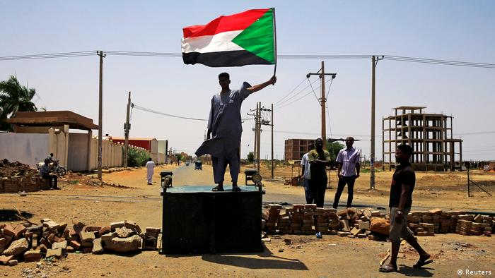 A protester stands on a block holding up the national flag (Reuters)