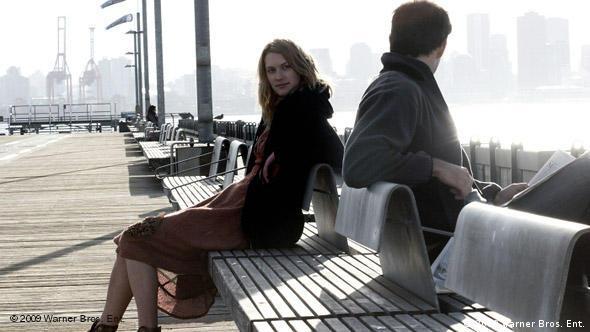 Eine junge Frau und ein Mann sitzen auf zwei Bänken am Meer (Foto: 2009 Warner Bros. Ent.)