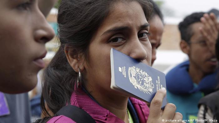 Venezuelana segura passaporte contra o rosto