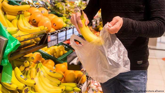 Pessoa coloca banana numa sacola plástica
