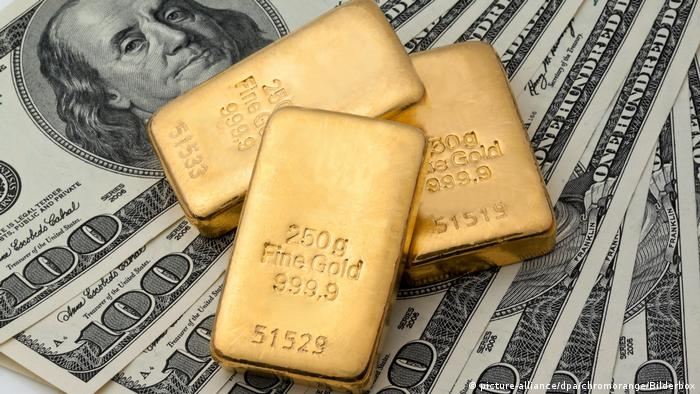 A representational image showing gold bars placed on $100 bills