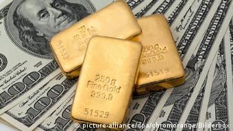 Золотые слитки на фоне купюр долларов