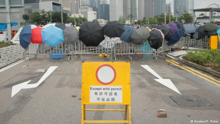 Umbrellas on a police barricade