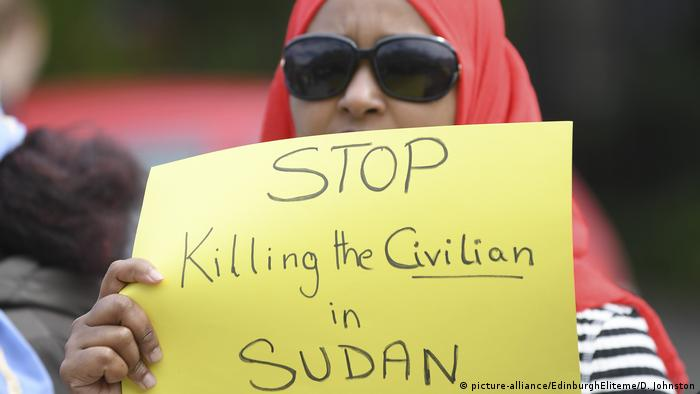 A Sudanese protester in Edinbugh holds up a poster reading Stop killing civilans in Sudan (picture-alliance/EdinburghEliteme/D. Johnston)