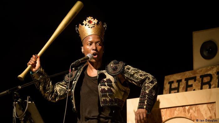 Die in Simbabwe geborene Künstlerin Nora Chipaumire steht mit einem Baseballschläger und einer Krone auf einer Bühne. (Ian Douglas)