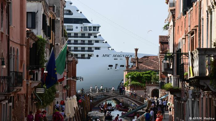 A cruise ship is seen from one of the canals leading to the lagoon in Venice, Italy
