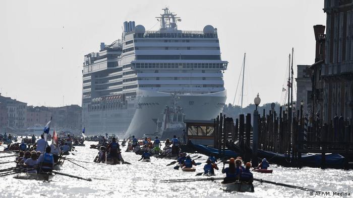 Pessoas em barcos a remo com navio de cruzeiro ao fundo