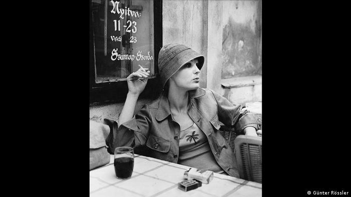 photo of woman sitting at a table and smoking