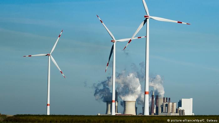 Windräder stehen vor dem Braunkohlekraftwerk Neurath