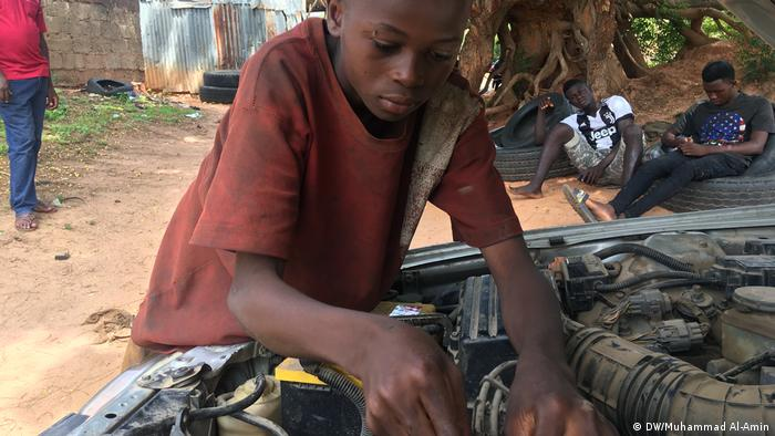 A young boy working on an engine