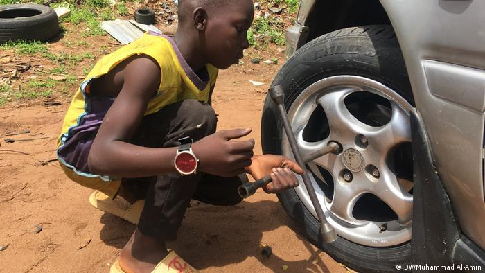 A boy changing a tire
