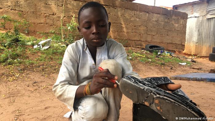 A 13-year-old boy working as a shoe shiner in Maiduguri, Nigeria