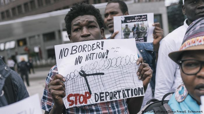 Protesters hold placards on anti-deportation.