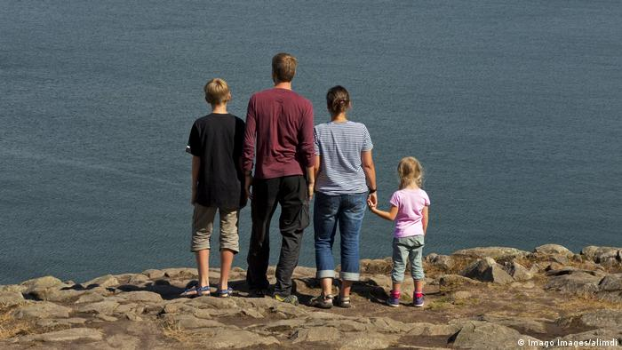 Family, father, mother with son and little daughter looking from cliff top over the sea