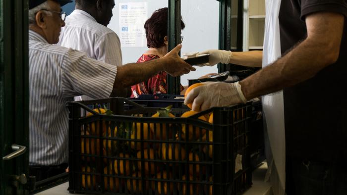 People queue to collect food at the Athens Reception and Solidarity Center (KYADA)