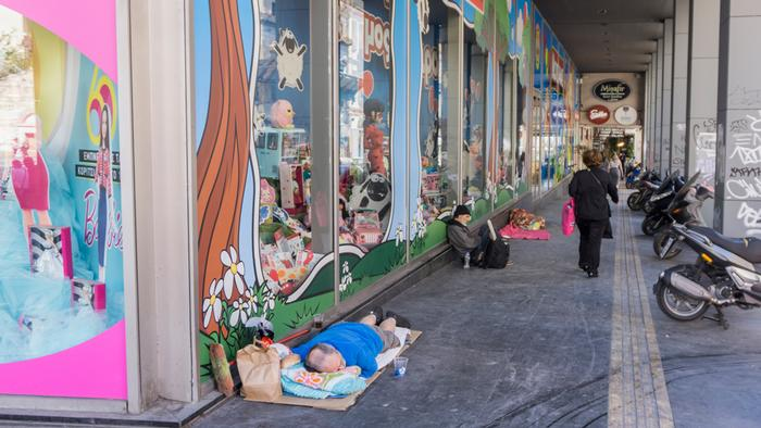 Homeless people sit and sleep on the ground next to a toy store in central Athens, near Monastiraki Square, one of the city's top tourist spots