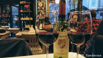 Two glasses of red wine and the bottle on a restaurant table in Montevideo