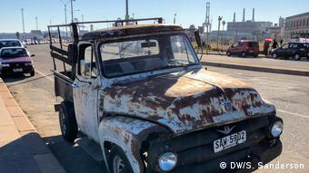 An old rusty pick-up truck parked on a modern road in Montevideo