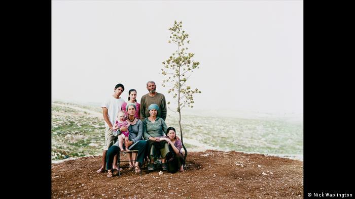 A photo of a family of seven, sitting outside on a hill (Nick Waplington)