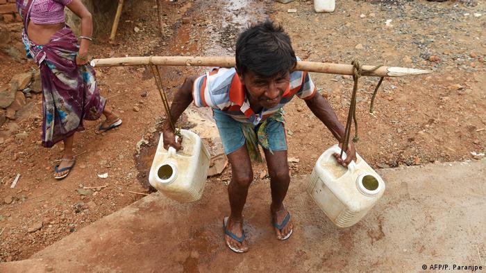 Um homem carrega água na Índia