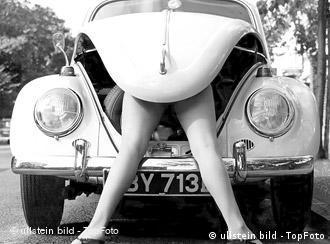 Frauenbeine schauen unter der Kühlerhaube eines VW Käfers hervor. (Foto: TOP Foto)