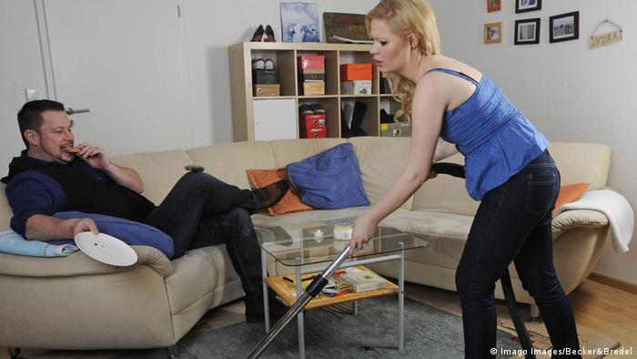 Man lying on sofa, woman vacuuming