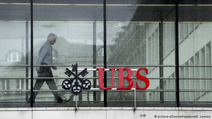 Man about to walk behind UBS logo on the Zurich branch