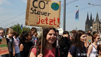 Демонстрантки требуют налога на выбросы CO2.