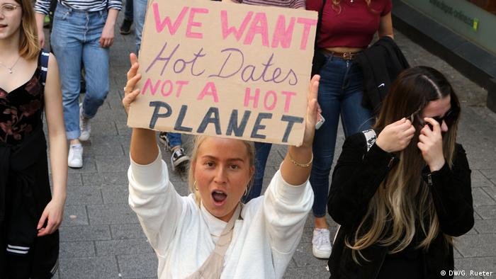 people at Fridays for Future demo, woman holding placard