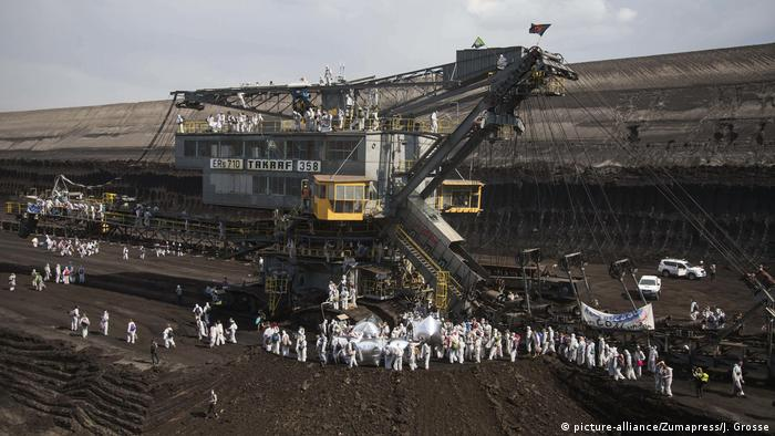 Protestors in front of some large machinary at an open-pit coal mine
