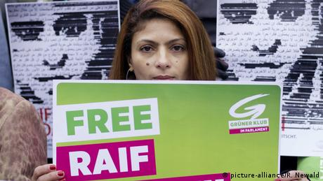 Ensaf Haidar hold sup a sign calling for the release of her husband, Raif Badawi (picture-alliance/R. Newald)