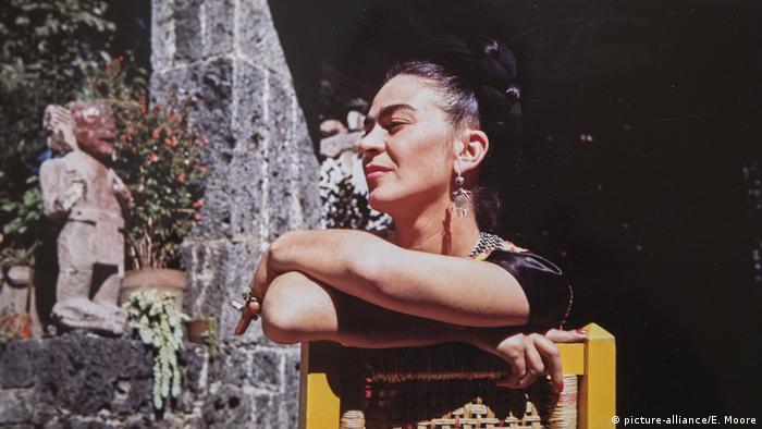 Malerin Frida Kahlo sitzend, die Arme über einer Stuhllehne verschränkt (picture-alliance/E. Moore)