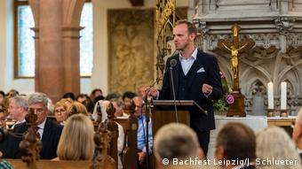 Un homme prononce un discours au pupitre d'une église, entouré d'auditeurs