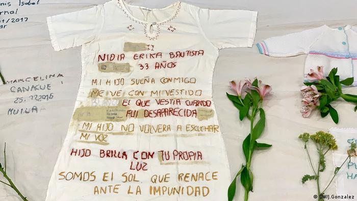 Auf ein Stück Stoff alter Kleidungsstücke des Opfer haben Angehörige Botschaften gestickt (DW/J.Gonzalez)