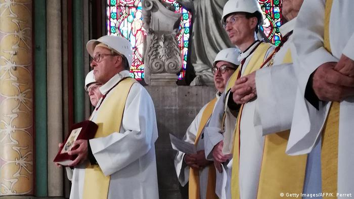 Celebrants in hard hats for the first Mass in Notre Dame Cathedral since a major fire two months ago