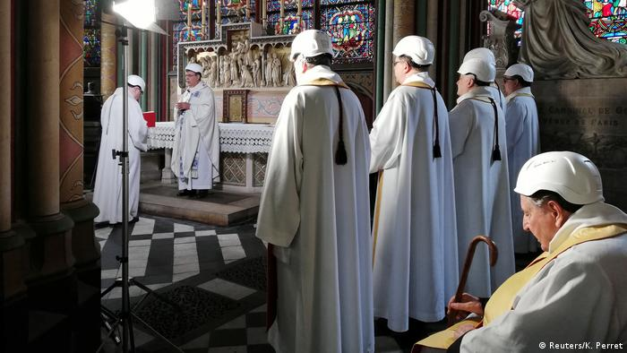 Priests in white robes surrounded by pillars and stained-glass windows