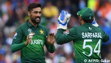Pakistan's Mohammad Amir (L) celebrates with Pakistan's captain Sarfaraz Ahmed after his dismissal of India's captain Virat Kohli during the 2019 Cricket World Cup group stage match between India and Pakistan at Old Trafford in Manchester, northwest England, on June 16, 2019. (Photo by Dibyangshu SARKAR / AFP) / RESTRICTED TO EDITORIAL USE