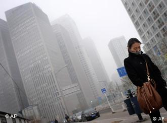 A Chinese woman walks past the Central Business District buildings shrouded by heavy fog in Beijing, China, Wednesday, Nov. 25, 2009. (AP Photo/Andy Wong)