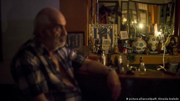A man stares off into the distance with a candle glowing in the dark during a power outage in Buenos Aires