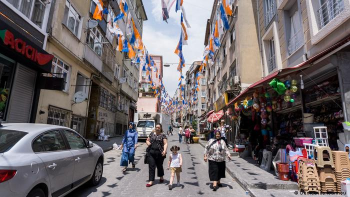 Women walk on the street under the flags of Erdogan's Justice and Development Party (AKP)