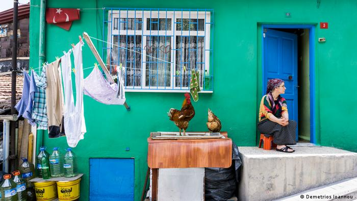 A woman feeds sits next to two chickens on the stoop outside of her home in Kasimpasa, Istanbul