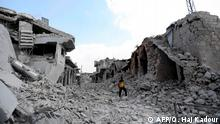 TOPSHOT - A picture taken on June 14, 2019, shows a man walking amidst the debris of destroyed buildings in the town of Ihsim, in Syria's Idlib region. - The Idlib region of some three million people is supposed to be protected from a massive regime offensive by a buffer zone deal that Russia and Turkey signed in September. But it was never fully implemented, as jihadists refused to withdraw from a planned demilitarised zone. (Photo by OMAR HAJ KADOUR / AFP)
