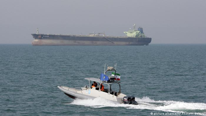 An Iranian Revolutionary Guard speedboat moves in the Persian Gulf while an oil tanker is seen in backgroun