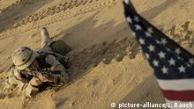 FILE - This Jan. 25, 2003 file photo shows an US soldier lying with his rifle in front of an American flag that hangs from a Humvee during live fire exercises in the Kuwaiti desert south of Iraq. Thousands of troops are assembling in Kuwait ahead of possible war with Iraq. President Barack Obama is poised to become the first U.S. leader in three decades to attack a foreign nation without broad international support or in direct defense of Americans. Not since President Ronald Reagan ordered an invasion of the Caribbean island of Grenada in 1983 has the U.S. been so alone in pursuing major lethal military action beyond a few attacks responding to strikes or threats against its citizens. (AP Photo/Laura Rauch, File) |