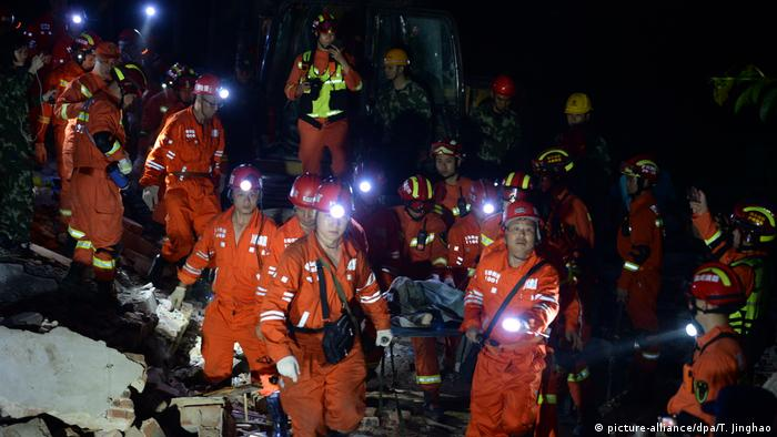 Rescuers in Yibin carry an earthquake victim from the rubble of a collapsed building