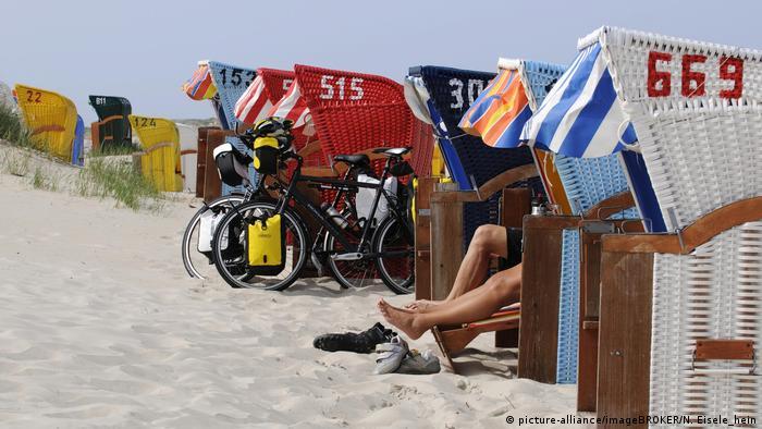 Strandkörbe, Fahrräder sind angelehnt und Leute sitzen darin