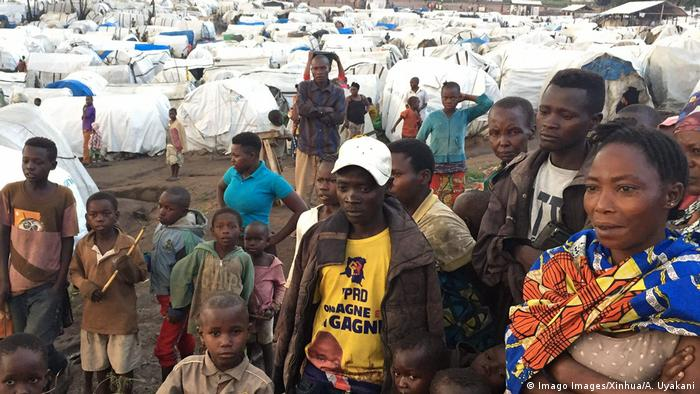 People standing in front of a refugee camp in the Democratic Republic of Congo (DRC)